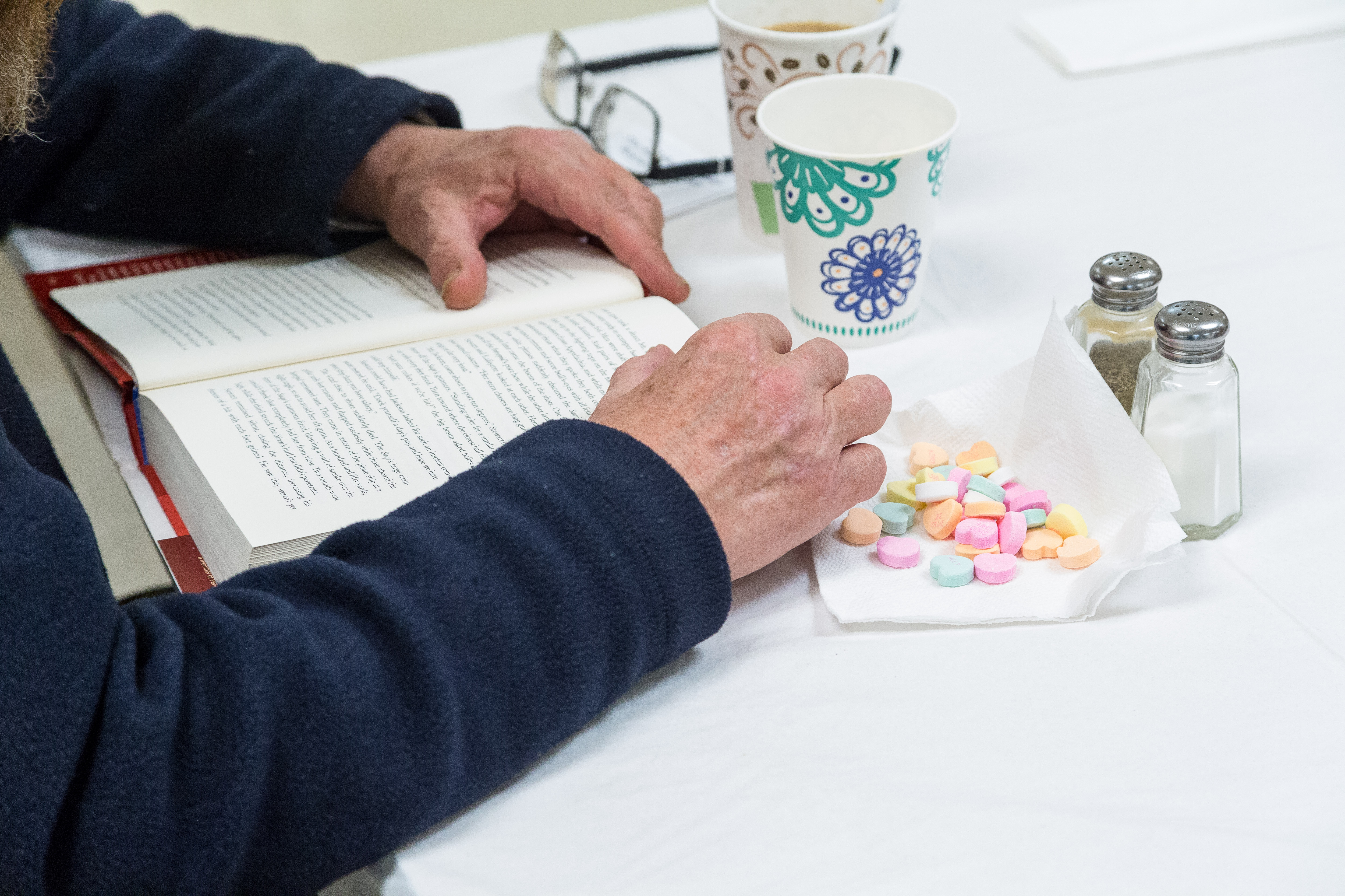 Picture of hands holding book with coffee & valentine candy